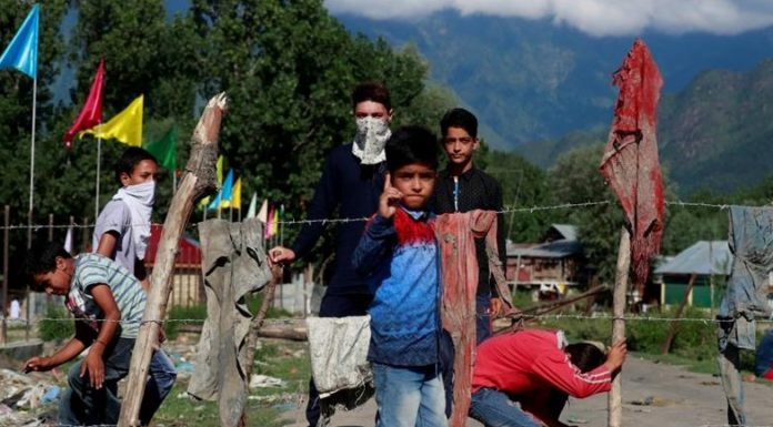 Kashmiri protesters stand